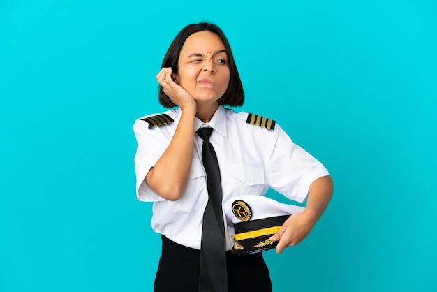 イライラして耳を覆っている孤立した青い背景の上の若い飛行機のパイロット