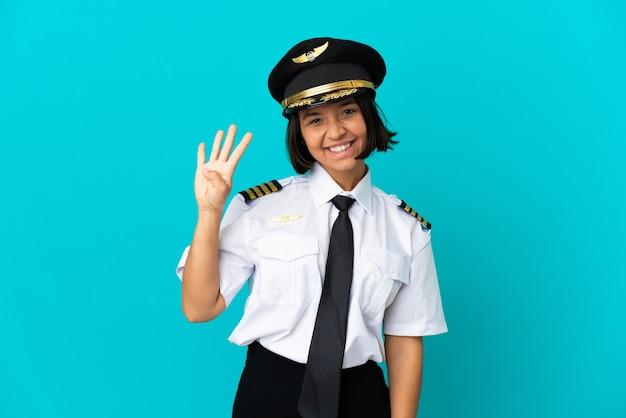 고립된 파란색 배경 위에 있는 젊은 비행기 조종사는 행복하고 손가락으로 4를 세고 있다