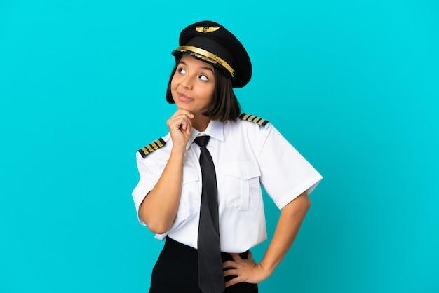 Молодой пилот самолета на изолированном синем фоне, сомневаясь