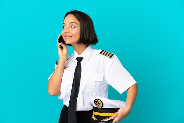 Молодой пилот самолета на изолированном синем фоне разговаривает с кем-то по мобильному телефону
