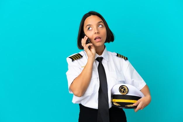 Молодой пилот самолета на изолированном синем фоне, разговаривая по мобильному телефону
