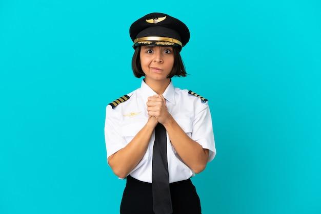 Молодой пилот самолета на изолированном синем фоне смеется