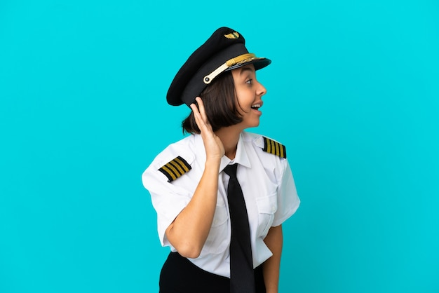 耳に手を置いて何かを聞いている孤立した青い背景の上の若い飛行機のパイロット