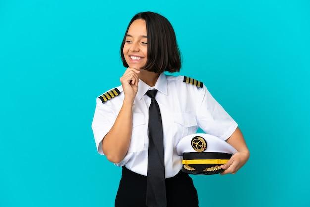 Молодой пилот самолета на изолированном синем фоне смотрит в сторону и улыбается
