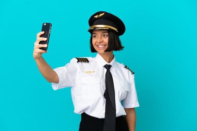 셀카를 만드는 고립 된 파란색 배경 위에 젊은 비행기 조종사