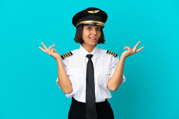고립 된 파란색 배경 위에 젊은 비행기 조종사 의심 제스처 만들기