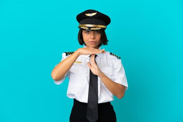 Молодой пилот самолета на изолированном синем фоне, делая жест тайм-аута