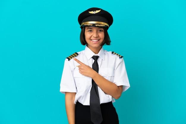 Молодой пилот самолета на изолированном синем фоне, указывая в сторону, чтобы представить продукт