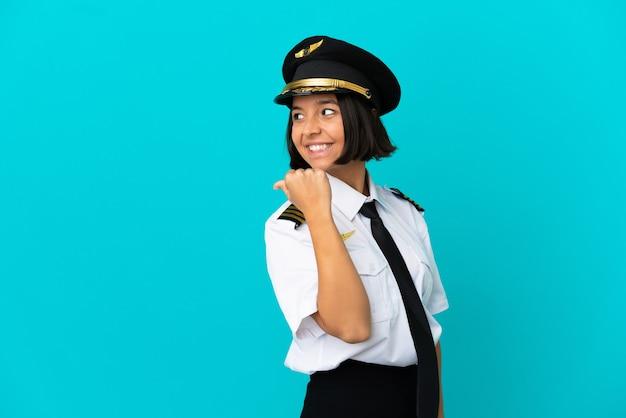 제품을 제시하기 위해 측면을 가리키는 고립된 파란색 배경 위에 젊은 비행기 조종사
