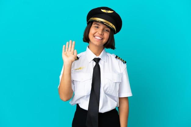 Молодой пилот самолета на изолированном синем фоне салютует рукой со счастливым выражением лица