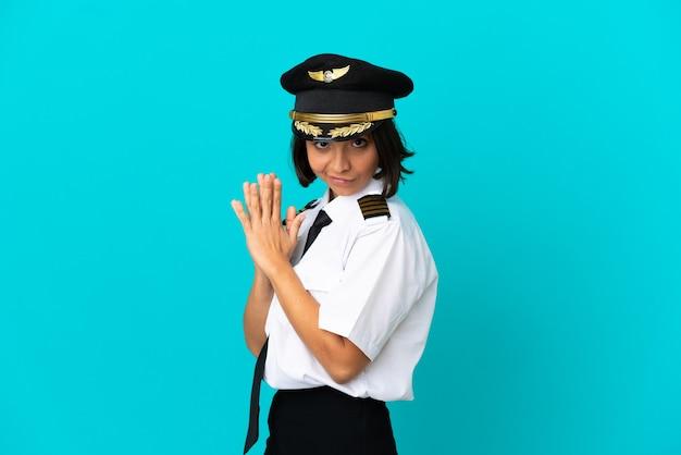 Молодой пилот самолета на изолированном синем фоне что-то замышляет