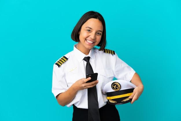 Молодой пилот самолета на изолированном синем фоне, отправив сообщение с мобильного телефона