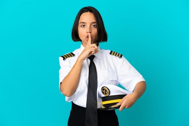 Молодой пилот самолета на изолированном синем фоне показывает знак жеста молчания, кладя палец в рот