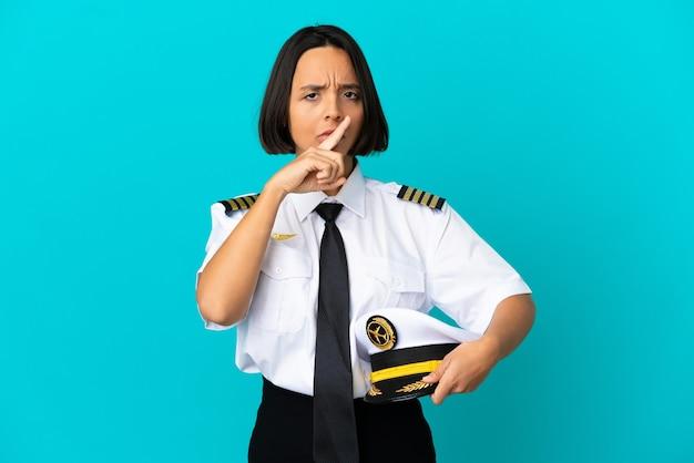 침묵 제스처의 표시를 보여주는 고립 된 파란색 배경 위에 젊은 비행기 조종사