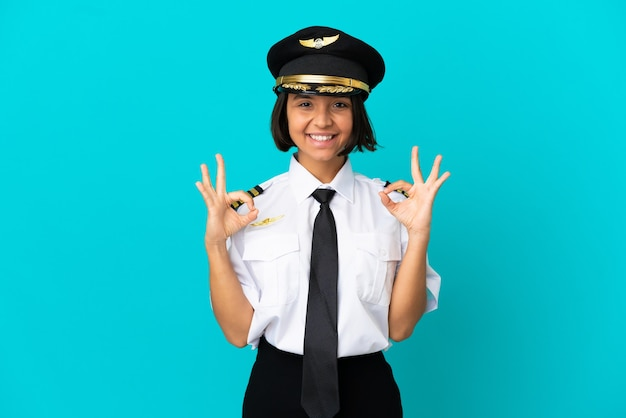 Молодой пилот самолета на синем фоне показывает знак ок двумя руками