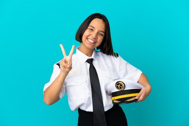 Молодой пилот самолета на изолированном синем фоне улыбается и показывает знак победы