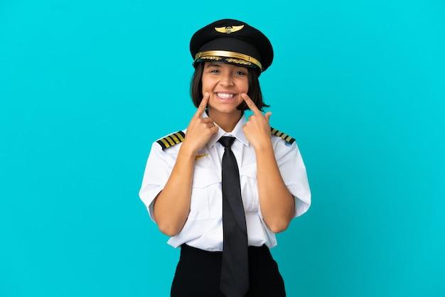 행복하고 즐거운 표정으로 웃고 있는 고립된 파란색 배경 위에 젊은 비행기 조종사