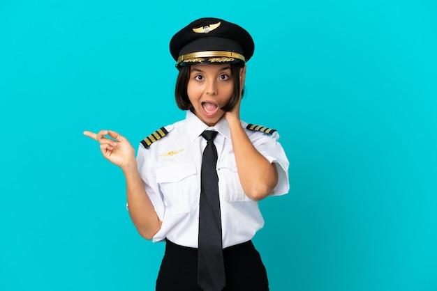 Молодой пилот самолета на изолированном синем фоне удивлен и показывает пальцем в сторону