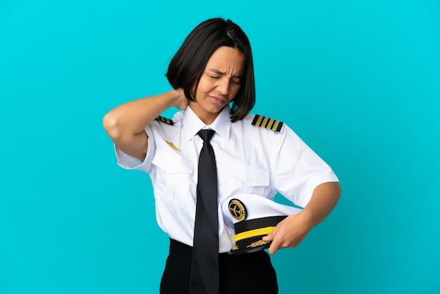 Молодой пилот самолета на изолированном синем фоне с болью в шее