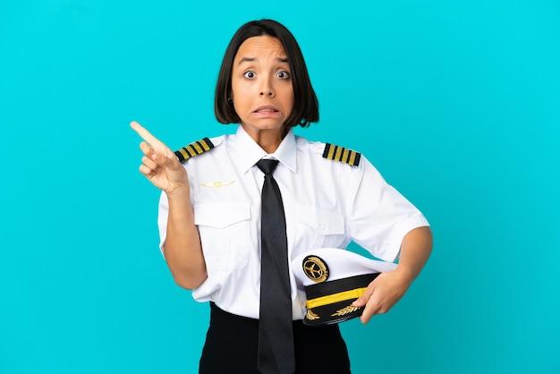 Молодой пилот самолета над изолированной синей стеной испугался и указал в сторону