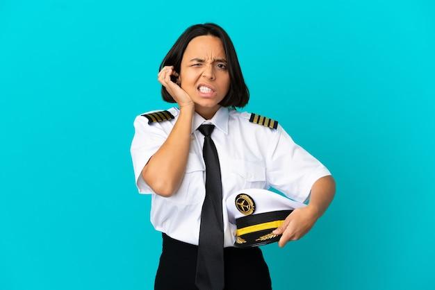 欲求不満と耳を覆っている孤立した青い壁の上の若い飛行機のパイロット