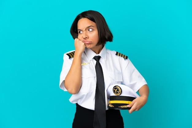피곤하고 지루한 표정으로 고립 된 파란색 벽 위에 젊은 비행기 조종사