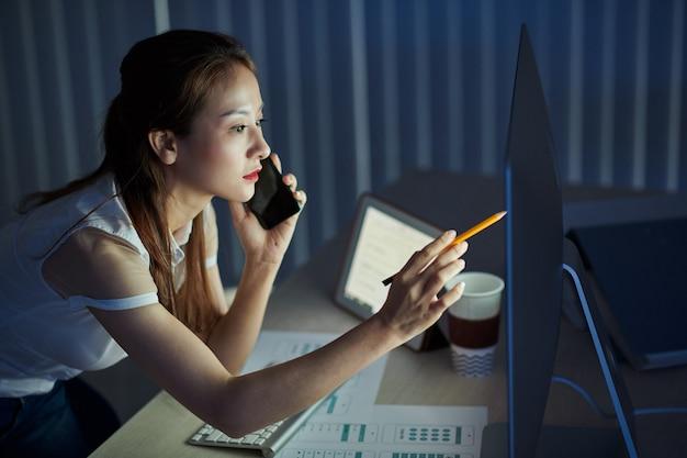 Молодой менеджер проекта айсан звонит по телефону, чтобы обсудить детали дизайна интерфейса мобильного приложения, когда остается в офисе поздно ночью