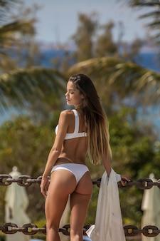 Young alluring woman in white bikini