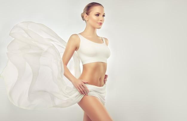 흰색 스포츠 속옷 날씬한 여성을 입고 우아하고 슬림 한 몸을 가진 젊은 매혹적인 여자