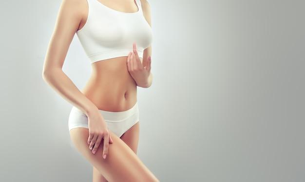 흰색 스포츠 속옷을 입은 우아하고 슬림 한 몸매를 가진 젊은 매혹적인 여성.