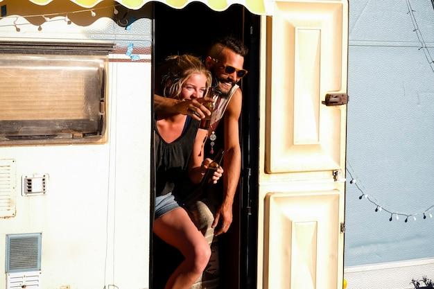 젊은 대안 밀레 니얼 커플은 오래된 캐러밴 작은 집 안에 서서 많이 웃습니다.
