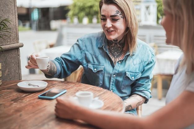 Молодая альтернативная женщина пьет кофе со своим другом в кафе-баре