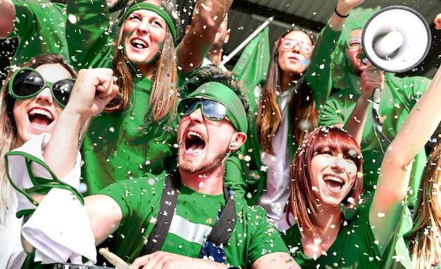 Молодые любители футбольных фанатов аплодируют с конфетти, наблюдая за матчем местного футбольного кубка на стадионе