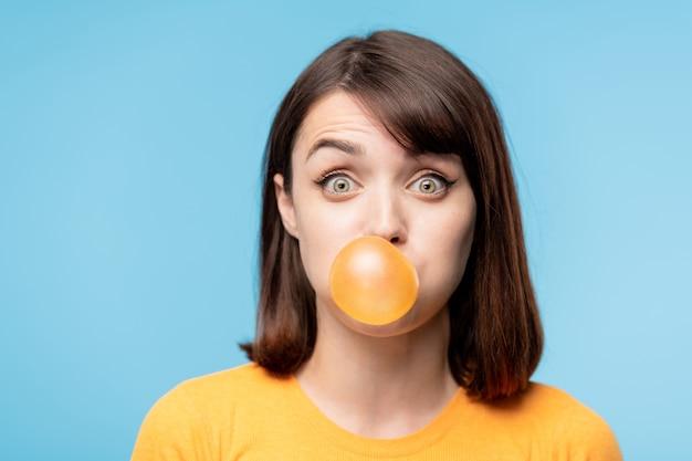 Молодая удивленная брюнетка смотрит на тебя, надувая пузырь жевательной резинки