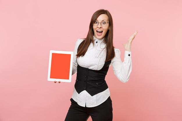 안경을 쓴 젊고 놀란 비즈니스 여성은 분홍색 배경에 격리된 빈 화면이 펼쳐진 태블릿 pc 컴퓨터를 들고 있습니다. 여사장님. 성취 경력 부입니다. 광고 공간을 복사합니다.
