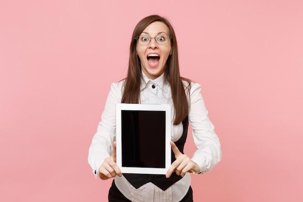 안경을 쓰고 입을 벌리고 있는 젊고 놀란 비즈니스 여성은 분홍색 배경에 격리된 빈 화면이 있는 태블릿 pc 컴퓨터를 들고 있습니다. 여사장님. 성취 경력 부입니다. 광고 공간을 복사합니다.