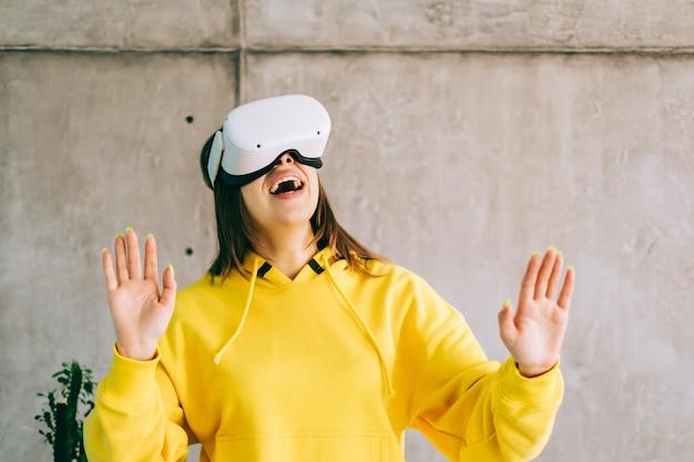 Молодая удивленная кавказская женщина с помощью гарнитуры vr, жестикулирует и смотрит вверх в виртуальной реальности.