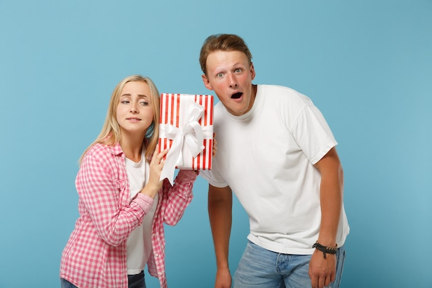 Young amazed couple two friends guy and woman in white pink t-shirts posing