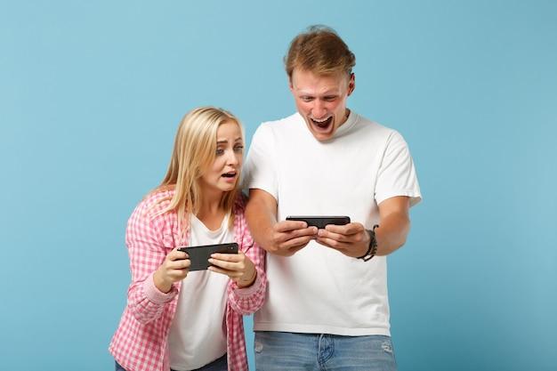 Giovane coppia stupita due amici uomo e donna in posa di magliette vuote rosa bianche