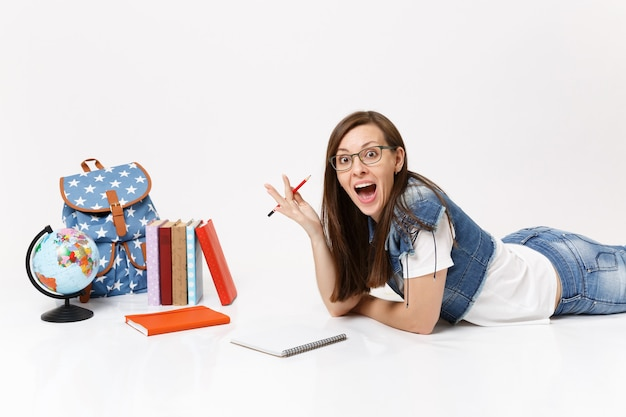 Young amazed excited woman student in denim clothes, glasses holding pencil notebook lying near globe, backpack, school books