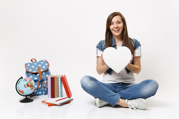 Young amazed exited woman student holding white heart with copy space and sitting near globe, backpack, school books isolated