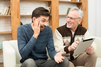 Young amazed guy and aged cheerful man using tablet on settee
