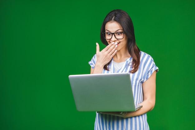 Молодые поражены счастливые улыбающиеся женщины в повседневную одежду, держа ноутбук и отправка электронной почты своему лучшему другу.