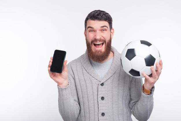 Молодой пораженный мужчина держит смартфон и футбольный мяч на белом фоне