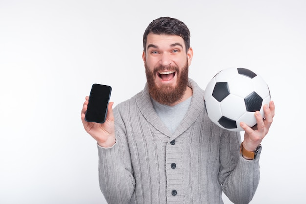Young amazed man holding smartphone and soccer ball over white background