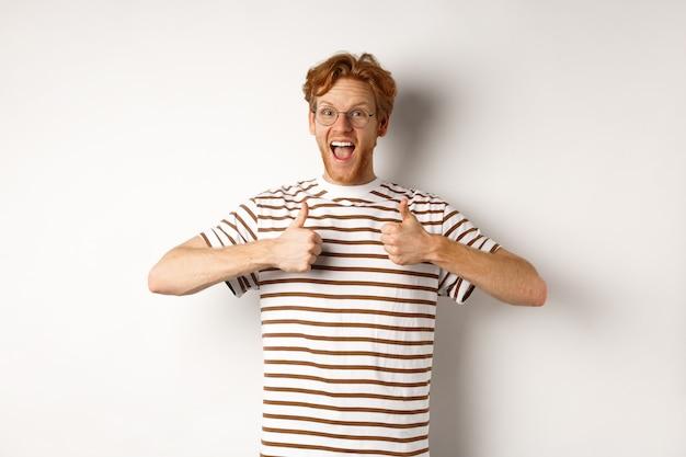 Молодой изумленный мужчина с рыжими волосами проверяет что-то удивительное, говорит «да» и показывает палец вверх, стоя на белом фоне.