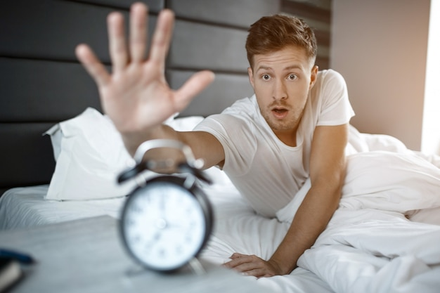 Young amazed man lyin on bed in morning. he overslept. guy reach clock.