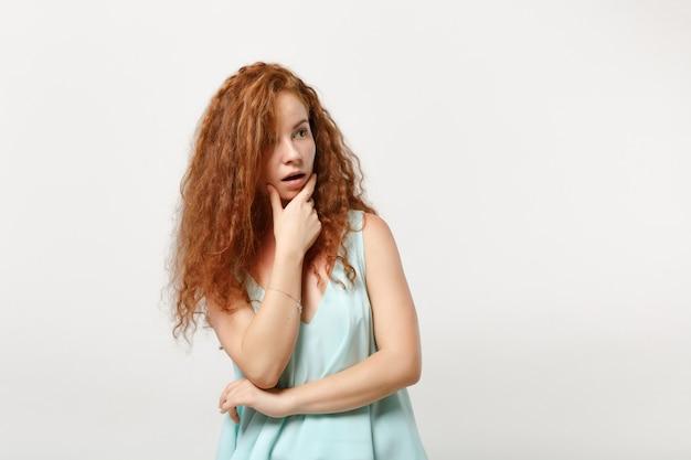 Giovane donna stupita rossa ragazza in abiti casual leggeri in posa isolata su sfondo bianco, ritratto in studio. concetto di stile di vita della gente. mock up copia spazio. metti la mano sul mento, guardando da parte.