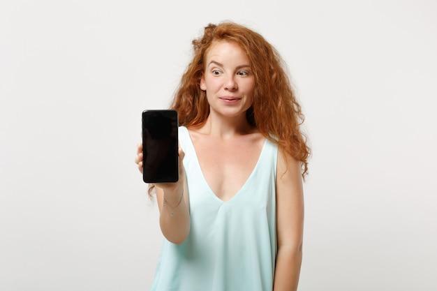 白い背景、スタジオの肖像画に分離されたポーズをとってカジュアルな明るい服を着た若い驚いた赤毛の女性の女の子。人々のライフスタイルの概念。コピースペースをモックアップします。空白の空の画面で携帯電話を保持します。