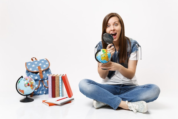 Young amazed surprised woman student looking on globe using magnifying glass learning sitting near backpack, school books isolated